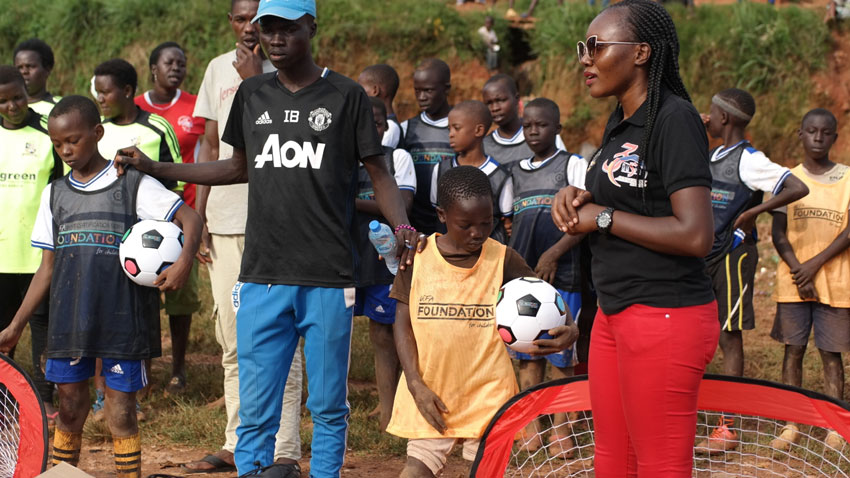 The founder of Aliguma Foundation Ritah Aliguma handing over the sports kits to the young football players in Acholi quarters Slums which were donated to them by the Uefa president Aleksander Ceferin last Friday