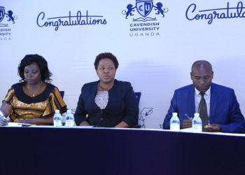Cavendish University's  Vice Chancellor Prof John Mugisha, and the Deputy Vice Chancellor, Dr. Olive Sabiiti (C) together with the Academic Registrar address the press