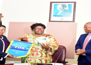 The Speaker (C) receives a ball and FIFA pennant from Samoura as FUFA President Magogo looks on