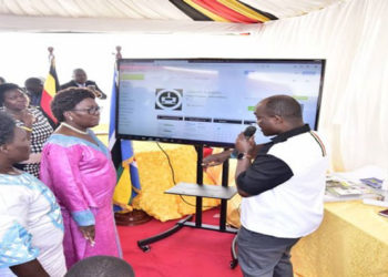 The Speaker(C) accompnaied by the Leader of the Opposition and Government Chief Whip listen to the Director, ICT Fred Bbale explain how the App works