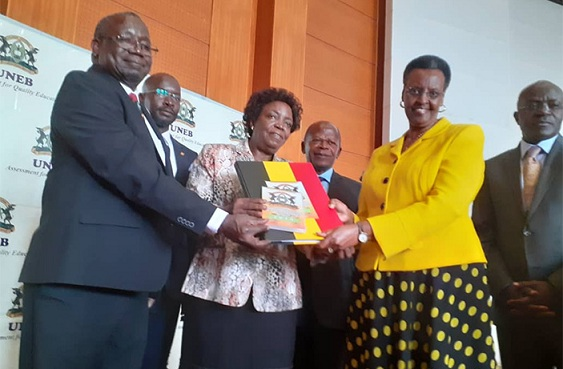 UNEB Executive Secretary Dan Odongo (L) , board chair Mary Okwakol (m) handing over the 2019 UACE results to education and sports minister Janet Museveni on Thursday