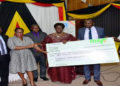 Speaker Kadaga (C) hands over a dummy cheque to the UPPA. On her left is Hon Kasolo Kyeyune with Hon Bahati(L) looks on