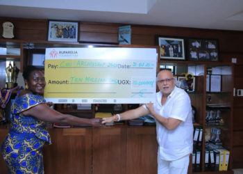 Dr Sudhir handing over a cheque to Ruth Nankabirwa