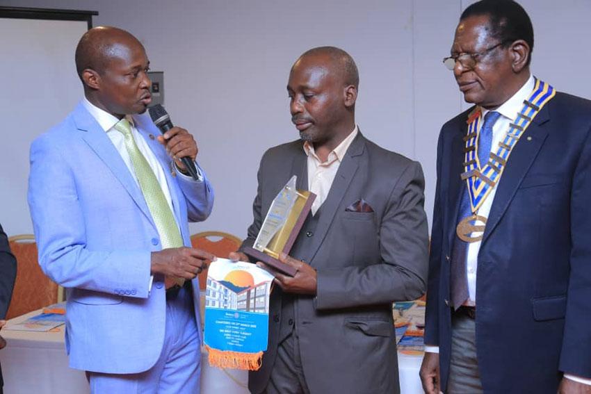 Dr. Michael Edgar Muhumuza receiving his award