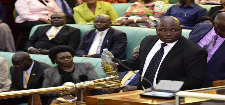 MP Abala holding a bottle containing locusts while in the House