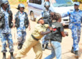 A police officer manhandling a journalist