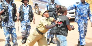 A police officer manhandling a journalist
