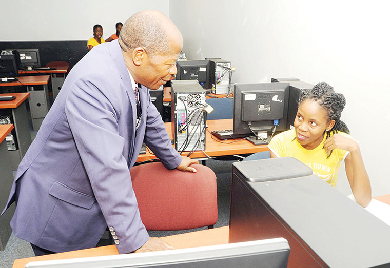 Minister-Chrysostom-Muyingo-engages-a-student-in-a-computer-lab.
