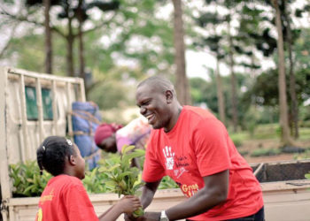 Environmentalist Joseph Masembe handing over a tree seedling to a kid
