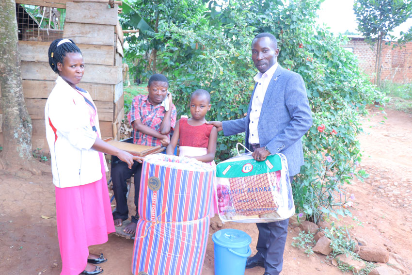Dorothy Nakiryowa receiving donated items; Bed sheet and a blanket from Gideon Kabenge who is currently taking care of his brother Ssebaduka.
