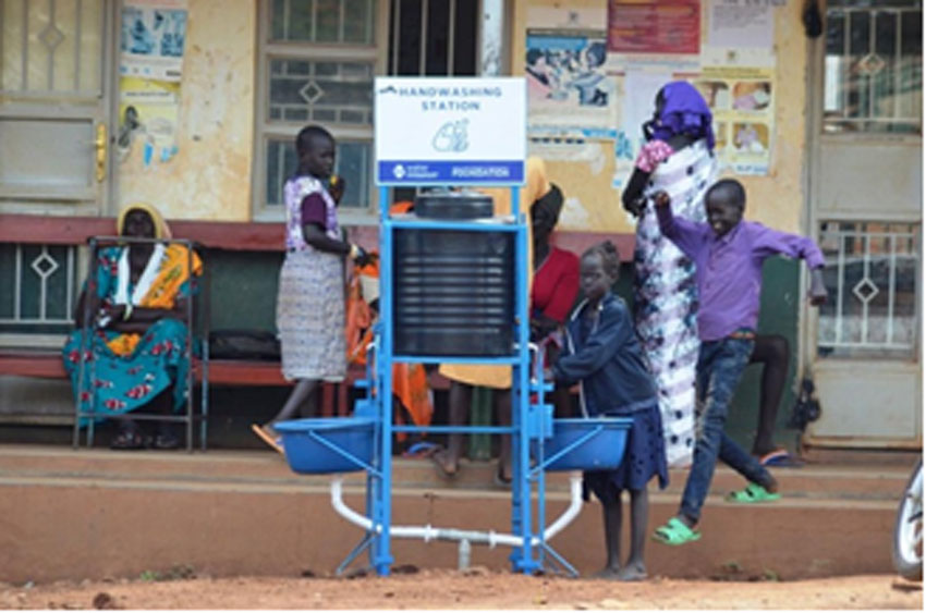 A refugee child washes her hands using a hand operated hand washing station at Kiryandong refugee settlement