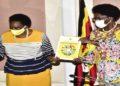 Minister Mary Karooro Okurut (left) hands over the SDGs report to the Speaker of Parliament Kadaga