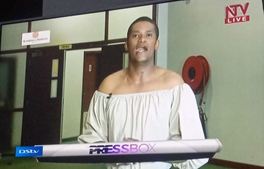 Andrew Kabuura putting on a dress on Monday
