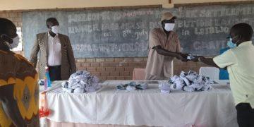 Mr. Robert Ocan, the Refugee Chairman receiving masks on behalf of refugees