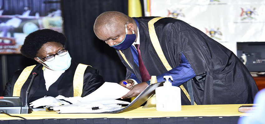 Speaker Kadaga(L) consults a clerk at Table during the debate on the NSSF Bill