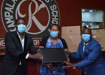 Mr Onyango Gareth, Mrs Daphine Kato handing over computers to Mr Solomon Serwanja