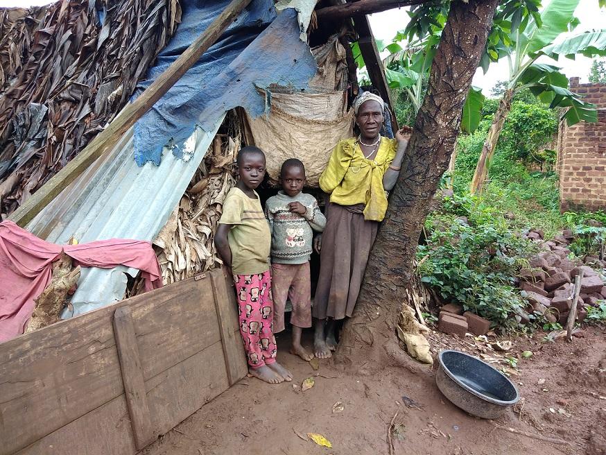 One of the beneficiaries  Josephine Nabwegamu with her grandchildren standing next to their substandard shelter