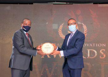 Uganda Insurers Association Chairman Latimar Mukasa hands over an award to a representative of one of the winners