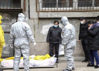 Funeral home workers remove the body of a person suspected to have died from the coronavirus outbreak from a residential building in Wuhan, Hubei Province, onFebruary 1, 2020.–CopyrightChinatopix via AP, File