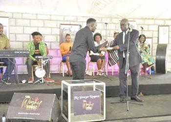 Pastor Bugembe receiving Shs10m from VP Ssekandi