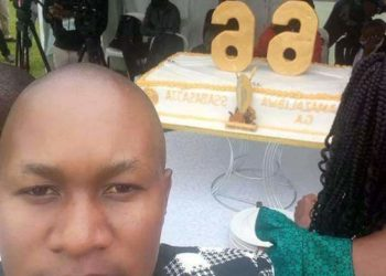 Kenneth Nsibambi and behind him is Kabaka's 66th birthday cake