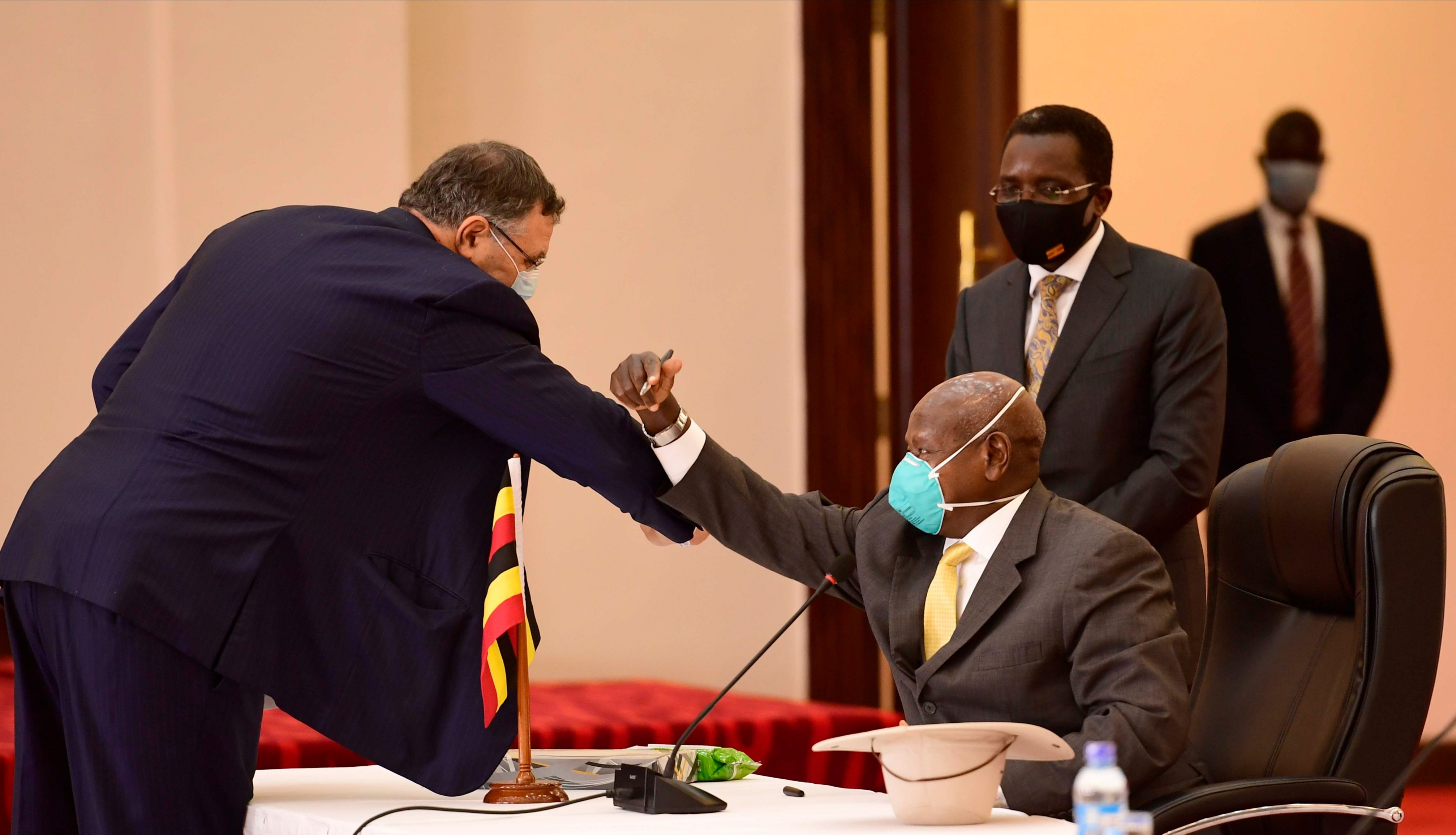 Total E&P President and Chief Executive Officer Patrick Pouyanne greets President Yoweri Museveni during the signing of three key oil and gas agreements