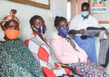 Anicia Filda in blue and white counsels women waiting for sterilisation at Atiak Health Centre IV