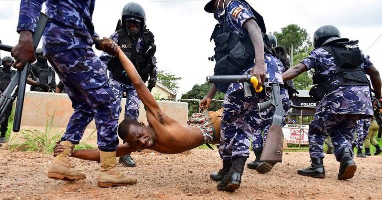 Police officers manhandling a Ugandan