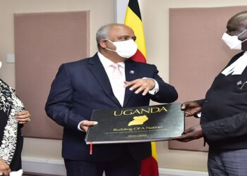 Oulanyah(R) hands a book about Uganda to Mehta. On the left is Mrs Mehta