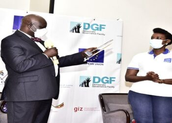 Oulanyah reads a citation before handing over an award to Sternford Moyo. Looking on is ULS President, Pheona Wall
