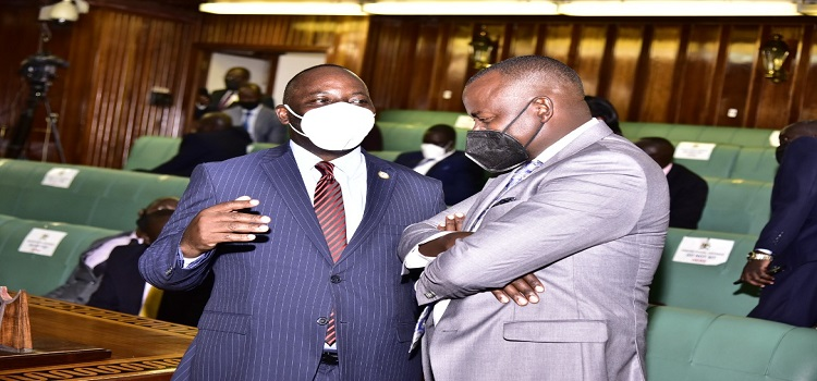 The LOP, Hon Mpuuga interacts with Minister Haruna Kasolo before the sitting of the House